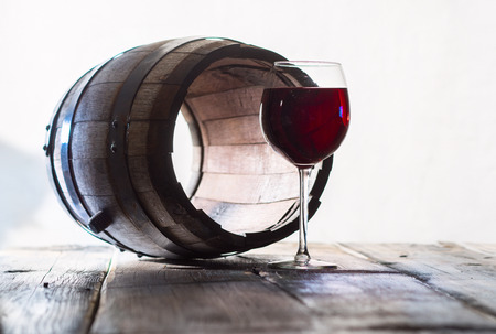 merrymaking: Glass of red wine and a old barrel without a bottom Stock Photo