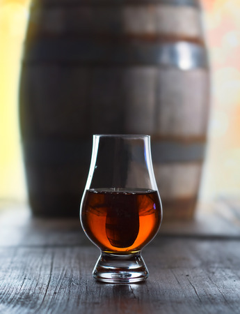 merrymaking: Glass of a whiskey and a old barrel at the wood table Stock Photo