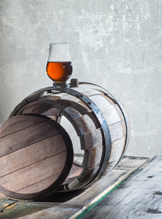 merrymaking: Goblet of a whiskey on a old barrel on a wall background