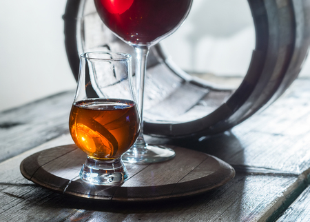 merrymaking: Wineglasses of wine and whiskey and old barrel on a table