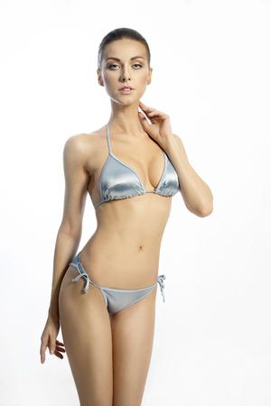 junge nackte m�dchen: Schlanke Frau in einem blauen Badebekleidung auf dem wei�en Hintergrund