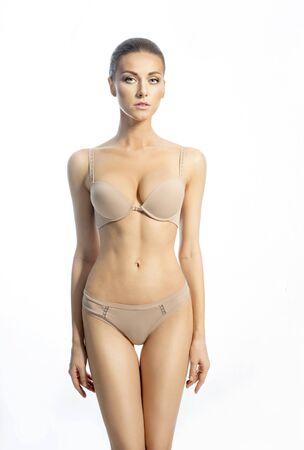 modelo desnuda: Mujer delgada en una ropa interior de color beige sobre el fondo blanco Foto de archivo