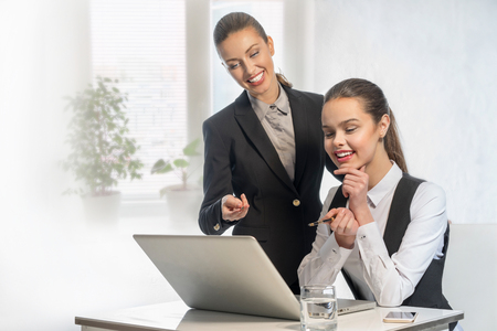 workmate: Two beautiful successful businesswomen work at the laptop in office