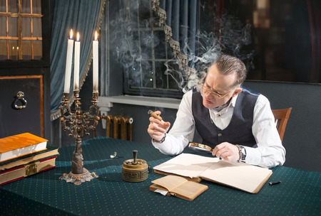 diamond candle: Elegant man sitting at a desk and looks through a magnifier in book