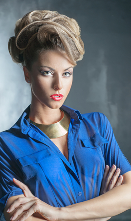 Portrait of the beautiful woman with the hairstyle and in blue blouse photo