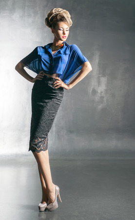 Pretty woman in the blue blouse and black skirt photo