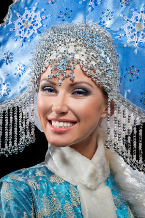 Portrait of a snow maiden with a beautiful crown on the black background