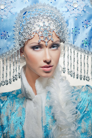 Portrait of a snow maiden with a beautiful crown on the white background