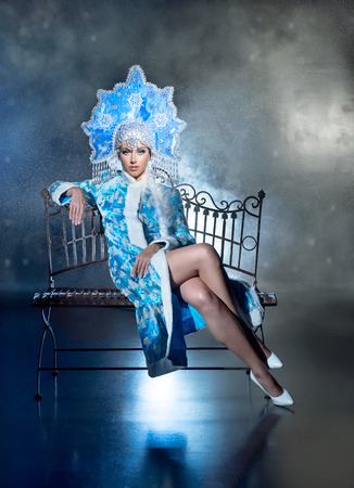 Beautiful snow maiden in a fur coat and  a crown is sitting on the bench Stock Photo