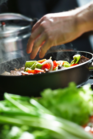 Chef cooks meat with a vegetables in a frying pan Stock Photo