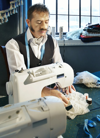 needle laces: Couturier sews a dress on the sewing machine in the studio