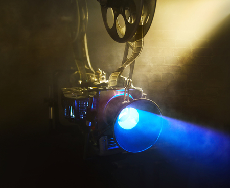 Old movie projector with the film on the brick wall background
