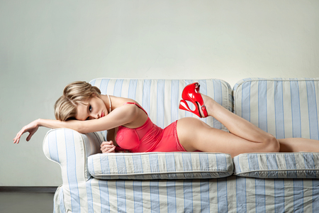 Sexy woman with a red lingerie lying on the sofa photo