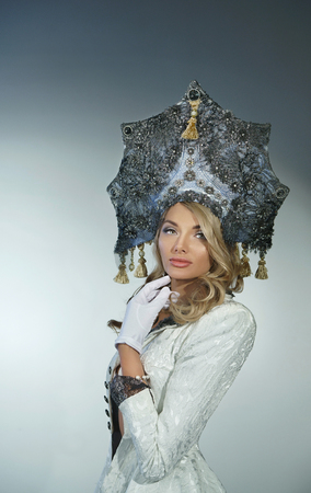 Portrait of a pretty snow maiden in a crown and coat Stock Photo