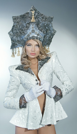 Portrait of a sexy snow maiden in a crown and white coat