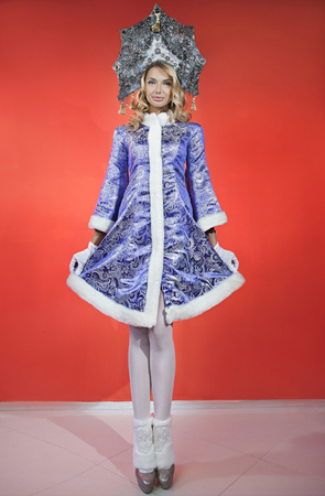 Beautiful snow maiden in a openwork blue crown and coat with a white fur
