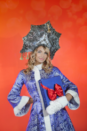 Happy snow maiden in a openwork blue crown and coat holds a blue box with a gift