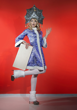Beautiful snow maiden in a openwork blue crown and coat with a white nameplate in his hands