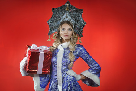 Beautiful snow maiden in a openwork blue crown and coat holds a red box with a gift
