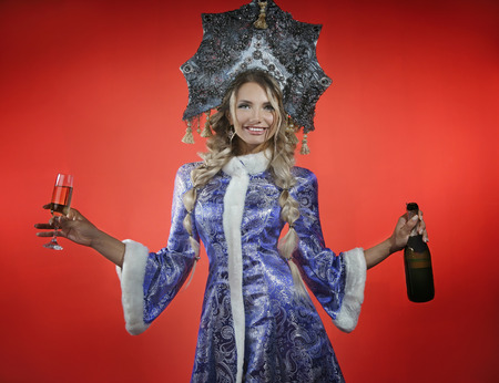 Beautiful snow maiden in a openwork blue crown and coat holds a red box with a a glass of champagne and bottle