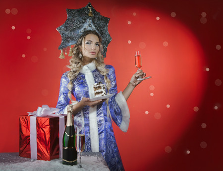 Beautiful snow maiden with a piece of cake, gift and champagne