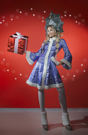 Beautiful Snow Maiden with a gift in a bright red box in his hand Stock Photo