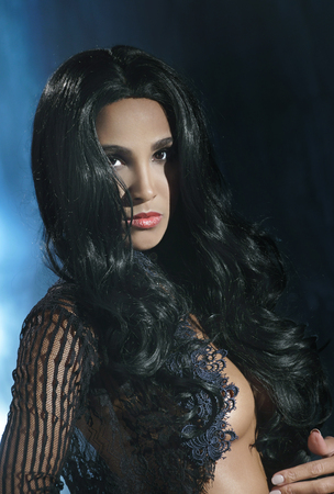 Portrait of a beautiful woman with long black hair in a black transparent blouse