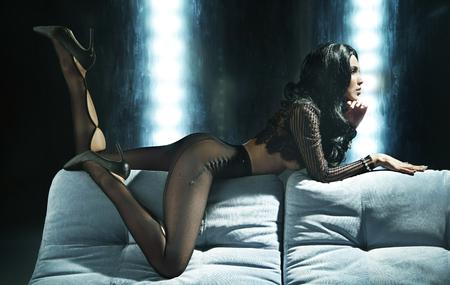 Sexy mooie vrouw in een zwarte transparante nylonkousen die op een bank liggen