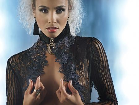 Portrait of a sexy woman in a black transparent blouse and accessory Foto de archivo