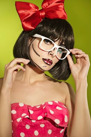 Portrait of funny mime girl with a theatrical makeup and red bow in a spectacles