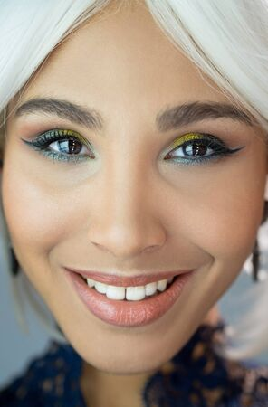 Cheerful face of a girl with a bright makeup and white hair Stock Photo