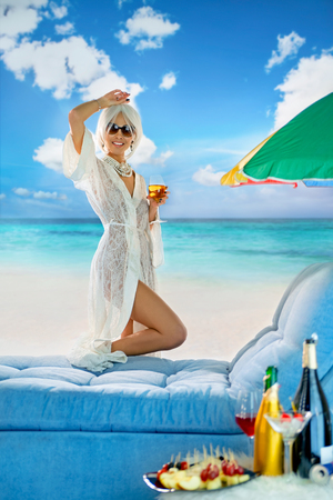 Luxurious woman on chaise lounge by the sea with a wine in a wineglass  Stock Photo