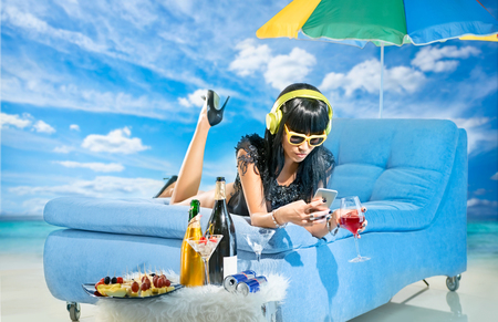 Woman wearing headphones and with mobile phone is listening to music on the beach Stock Photo