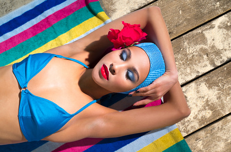 Woman in a blue swimsuit and  bathing cap is sunbathing on a towel on a wooden floor