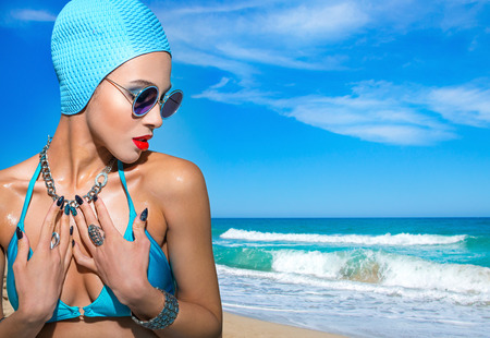 Portrait of a woman in a blue swimsuit, sunglasses and  bathing cap on a background of seascape