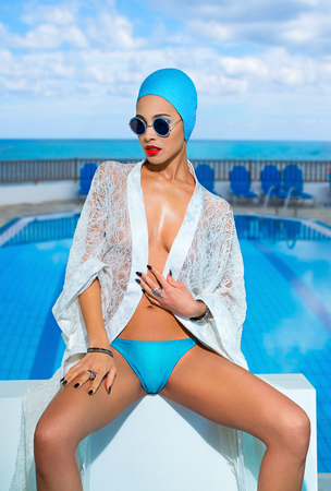 Beautiful woman in a blue swimsuit, sunglasses and  bathing cap by the pool near the sea