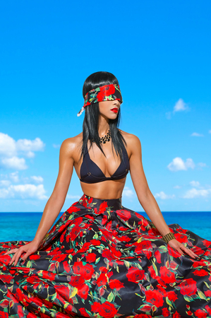 Beautiful girl in a black bra, colorful skirt and blindfold sits by the sea