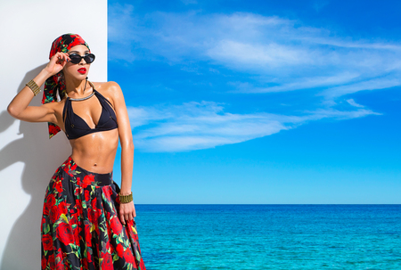 Slim woman in a black bra, bright bandanna and skirt on the background seascape