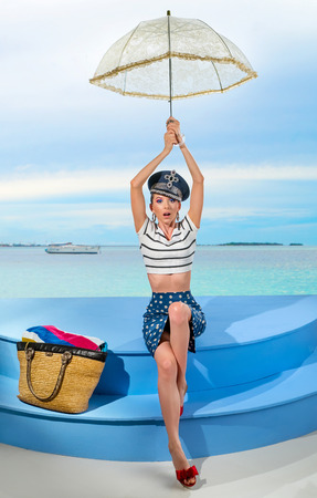 Beautiful girl in striped blouse and cap on yacht