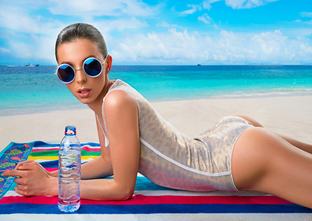 Beautiful woman in shiny white swimsuit with bottle of water on beach