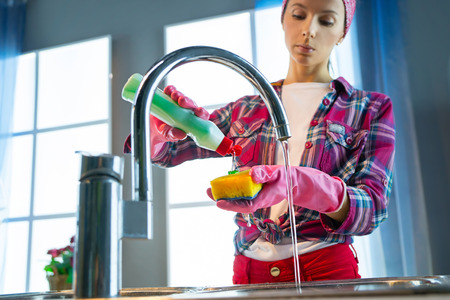 Woman in pink protective rubber gloves washes dishes in the kitchen with sponge Banque d'images