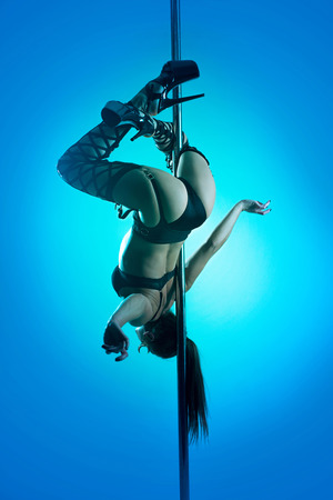 Slim woman in a black lingerie dancing on a pylon