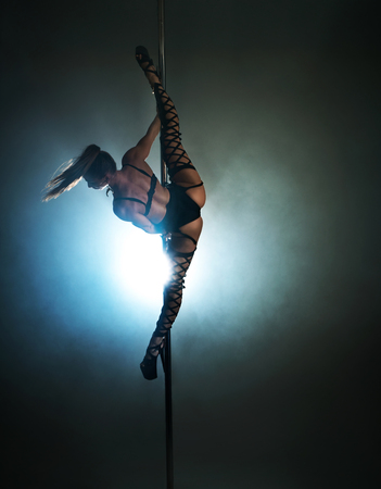 Sexy woman in a black lingerie dancing on a pylon