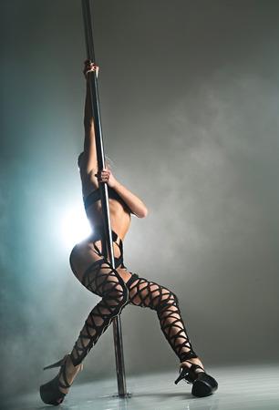 Schöne Frau in schwarzen Dessous tanzt auf einem Pylon