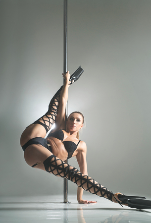 Beautiful woman in a sexy black lingerie dancing on a pylon