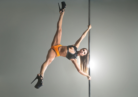 Beautiful woman in a lingerie dancing on a pylon