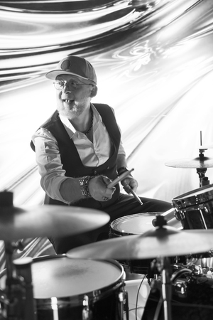 Cheerful drummer playing on drum set on stage in the color light