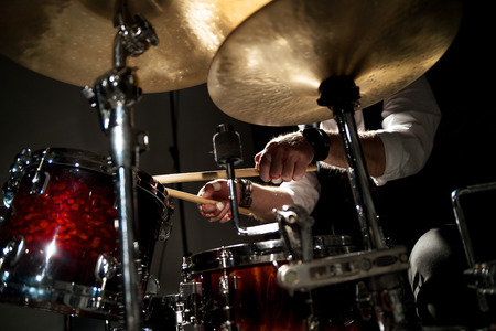 Drummer with a drumsticks in his hands playing on drum set on stage on the black background Imagens