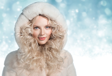 Beautiful woman in luxury light mink fur coat with hood on winter background 스톡 콘텐츠