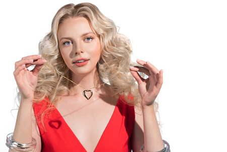 Woman in red dress keeping heart shape jewelry. Concept of wealth and luxurious life